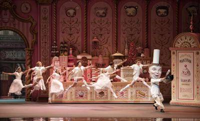 group of dancers leaping towards a Baker character in a sweet shop
