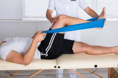 Physiotheapist helping a laid down patient with a theraband leg exercise