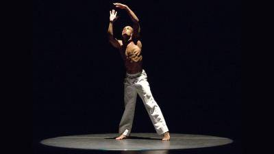 Kirven Douthit-Boyd performing a solo in white pants in a spotlight