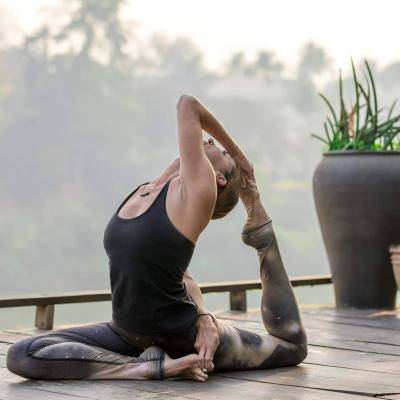 Allison Gomes in a toe lockYoga position, on an outside deck