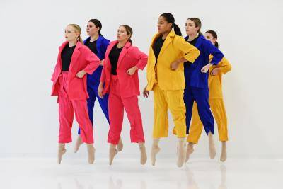 emme dance collective dancers in colorful suits jumping on a white background