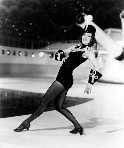 Eleanor Powell on set in a black tight costume and hat, leaning back with one leg extended front