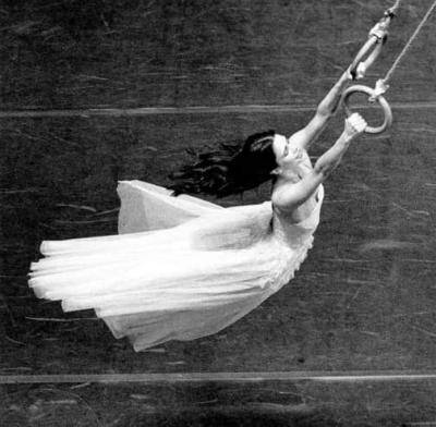 overhead view of Pina Bausch in a long white dress holding on to gymnastic hoops