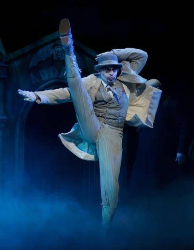 Julio Cataño-Yee doing a high kick in a stage performance of The Addams Family