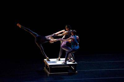 Two dancers holding a third in a penché, all standing on a small platform