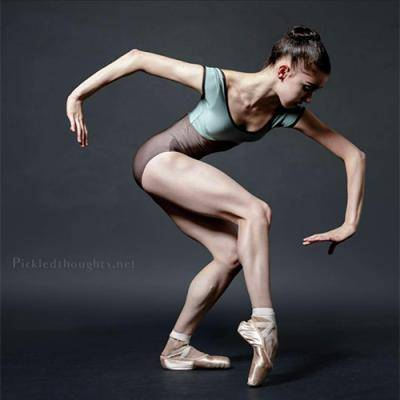 Ballerina Tania Angelovski posing in a mint and brown colored leotard, against a dark grey background