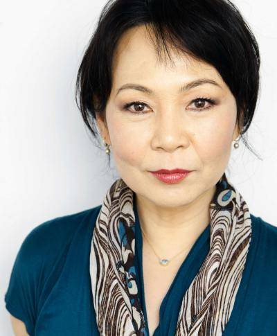 portrait of Cindera Che, in a green blouse and a scarf around her neck