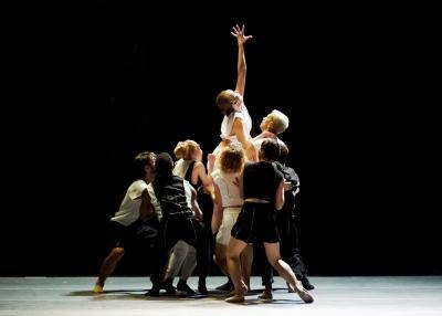 Group of dancer together lifting one female dancer as she reaches upward