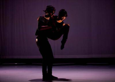 LA Contemporary Dance Company duet performers on a dark lit stage