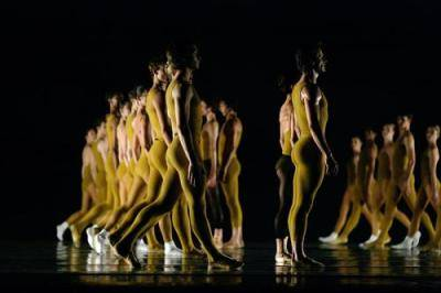 lines of dancers in yellow unitard on a dimly lit stage