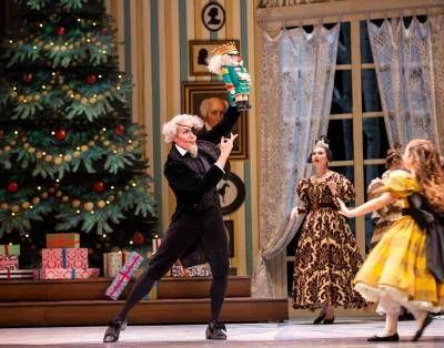 Pacific Northwest Ballet scene of Drosselmeyer brandishing a Nutcracker toy in front of a Christmas tree