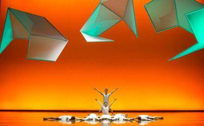 2 dancers in white making a V shape with their arms, while other dancers are laying on a ground, on a bright orange lit backdrop and green shapes up top