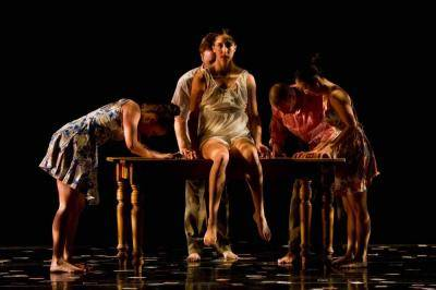 Drea Sobke sitting on a table, surrounded by other dancers with their heads down