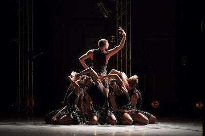 LA Dance Project performing: one dancer facing back standing surrounded by group kneeled around facing out