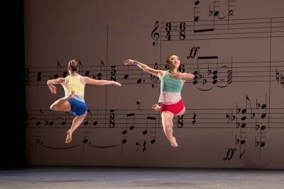 2 dancers in a stag leap in opposite direction, background of a projected music sheet