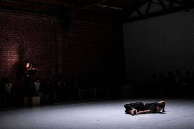 one dancer alone laying on the stage floor, moody lighting