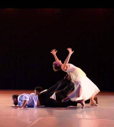 female dancer in a white dress leaning back onto 2 dancers feet, as they lay on the flat facing the floor