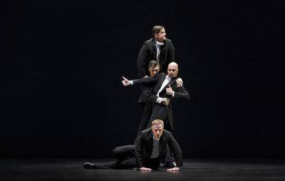 4 male dancers in business suits in a tower pose
