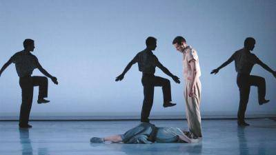 male dancer standing and looking down at another dancer laying on the floor at their feet