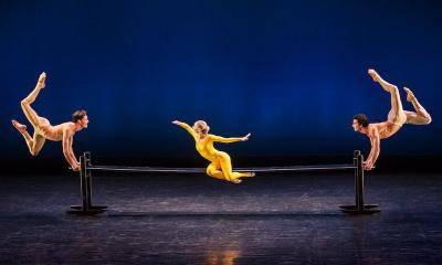 female dancer in yellow unitard on a bench with one male dancer on either side doing a stag leap