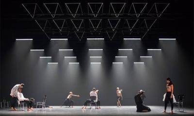 A group of dancers scattered across a stage, some on chairs some standing, some alone, some in duets. all wearing black and white.