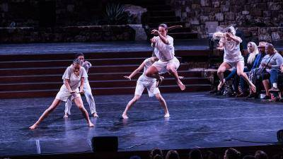3 dancers center stage leaning over to the right, 2 dancers upstage left jumping with knees bent