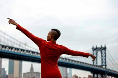 back of a Black woman in a red long sleeve shirt stretching arms out in front of the Brooklyn bridge