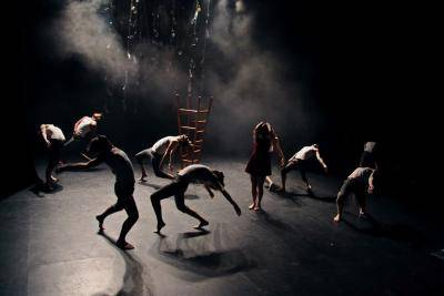 group of dancers in various moves scattered across the stage on a dimmed stage