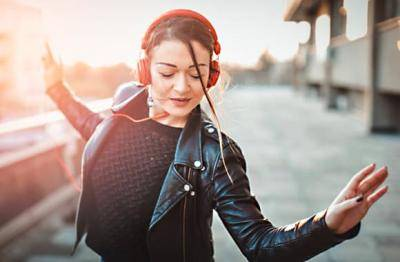 Young women with red headphones and a leather jacket, dancing in the street