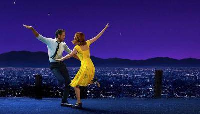 Emma Stone in a yellow dress and Ryan Gosling in a shirt and tie, dancing together against a hollywood night backdrop