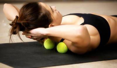 Young women rolling her shoulders over tennis balls