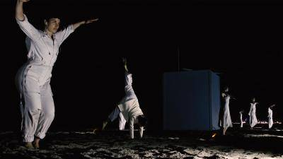 "performers in white maintaining social distance on a beach at night in Corinna Kinnear's ""Ocean12"""