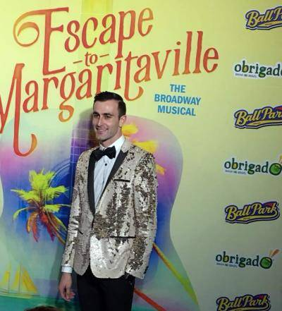 performer Justin Keats wearing a glitter gold suit jacket in front of the Escape to Margaritaville press wall