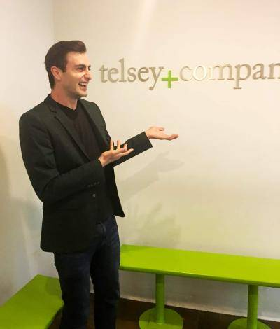 Broadway performer Justin Keats showing the Telsey+Company logo on their office wall