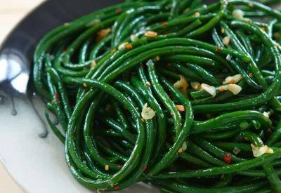 Long string beans cooked with pieces of garlic on a plate