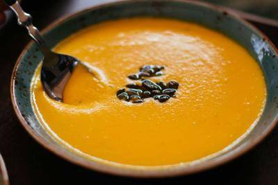 spoon in a bowl of pumpkin soup, with roased sunflower seeds