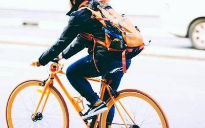 back view of a cyclist with an orange backpack, on an orange rimmed bicycle