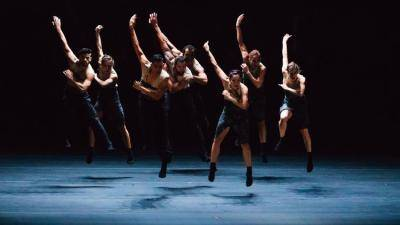 group of dancers in black jumping, with one arm up