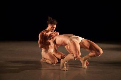 one dancer arching back while another is holding him his head