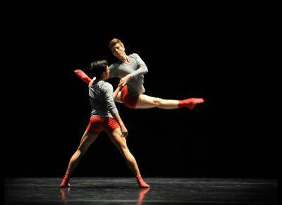 Two male dancers, in red socks and shorts, and grey top, one jumping