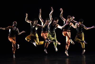 group of male dancer with colorful pants on a black background