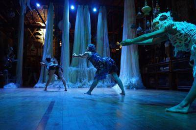 3 female dancers leaning forward on a blue green lit stage
