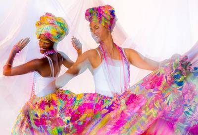 2 female dancers in a white top and pink colorful big skirts and head pieces
