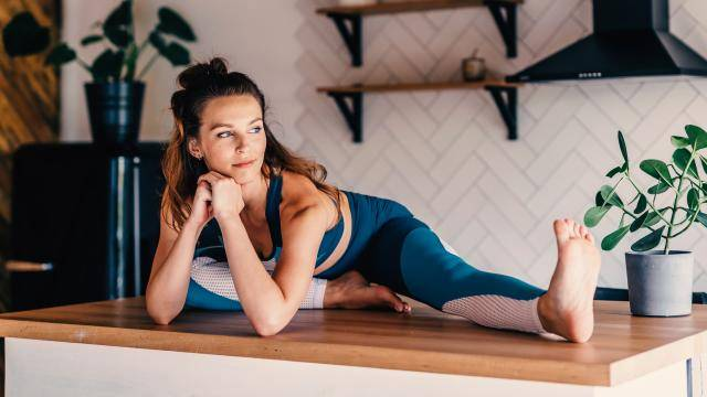 woman stretching on top of kitchen counter