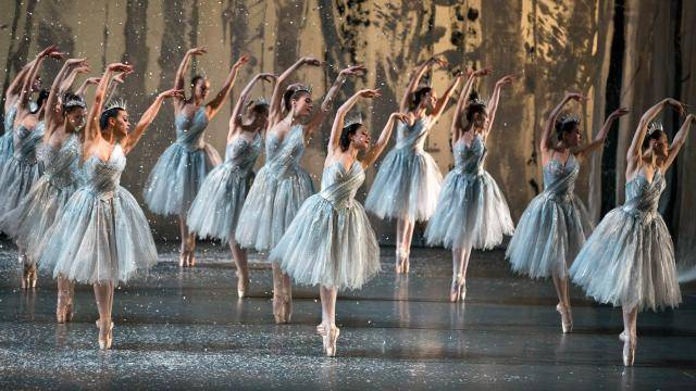 3 rows of dancers in a 5th position on pointe, donning silver mid length tutus, with snow falling.