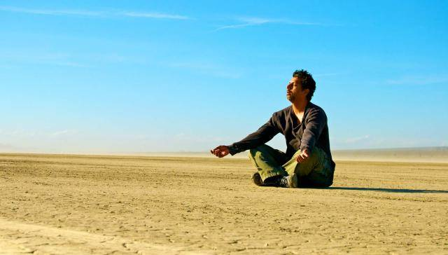 Alex Magno sitting and  meditating in the desert, on a clear blue sky backdrop.