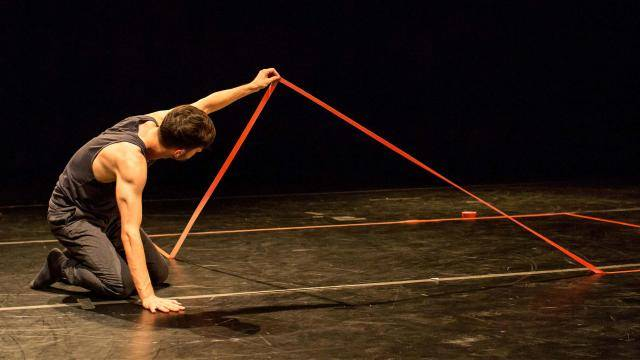 Andrew Pearson lifting red tape off marley floor in his performance at LA Dance Festival 2017.