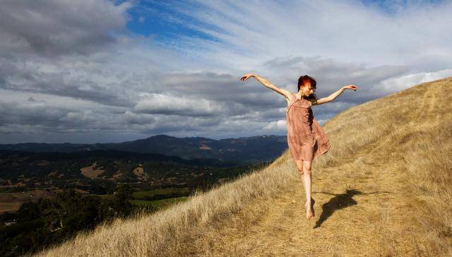 Dancer Jordan Hayes in a light color sundress jumping outdoors on a blue sky background.