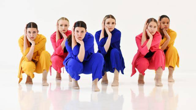 emme dance collective dancers crouching in colorful suits on a white background