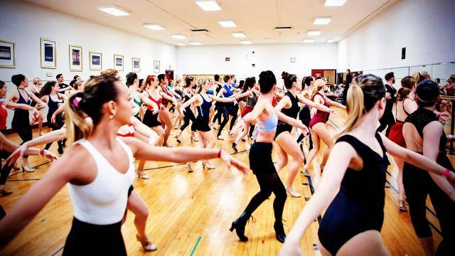 A huge group of dancers learning a routine at a Rockettes audition.